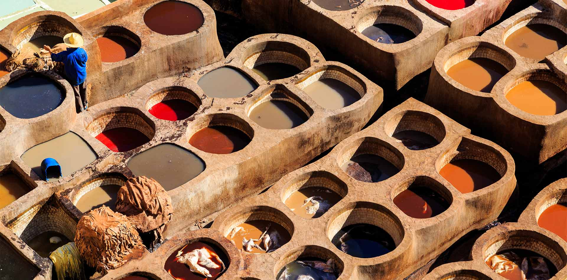 Africa Morocco Fes historic traditional tannery man soaking leather in colorful dye - luxury vacation destinations