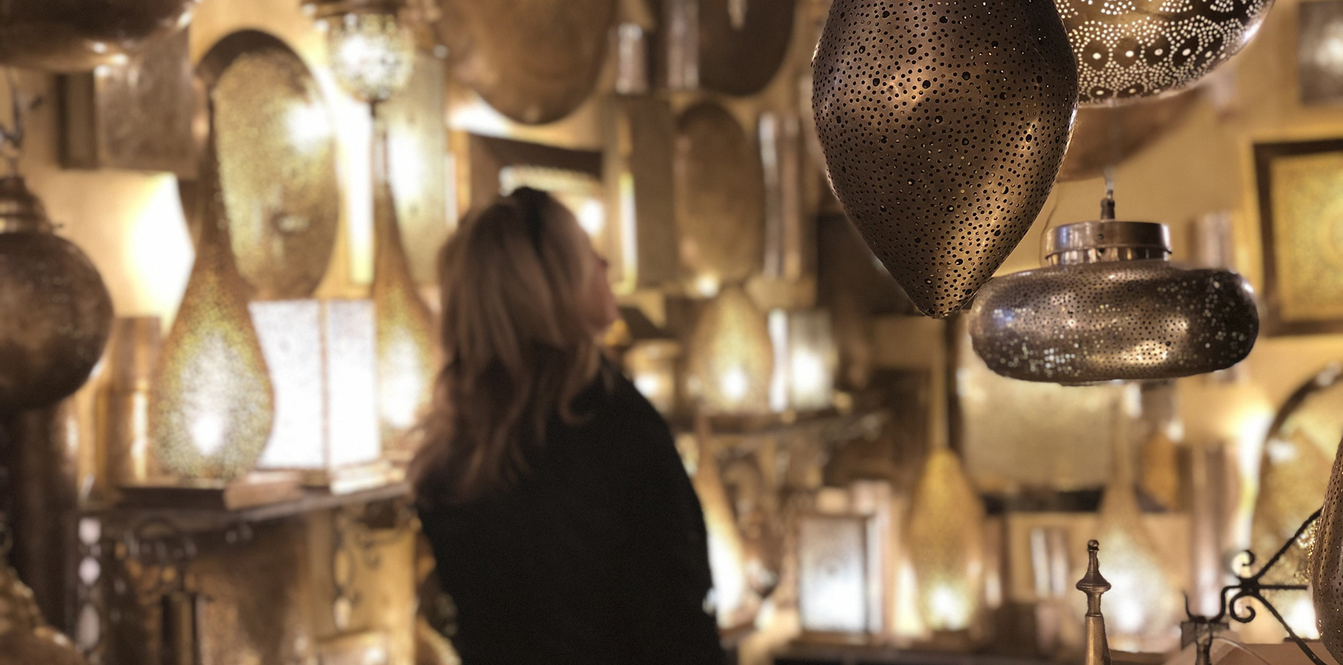 Africa Morocco woman looking at traditional brightly lit decorative lanterns in souk - luxury vacation destinations