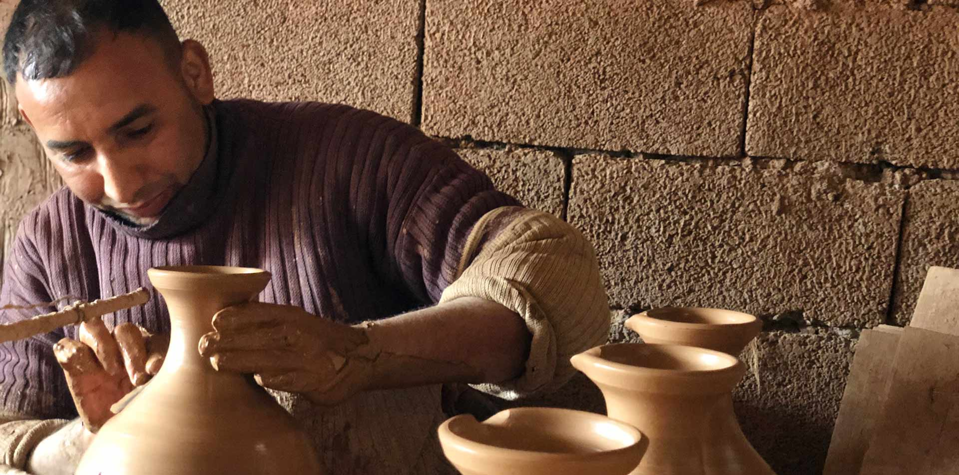 Africa Morocco local man molding clay into traditional handmade pottery - luxury vacation destinations