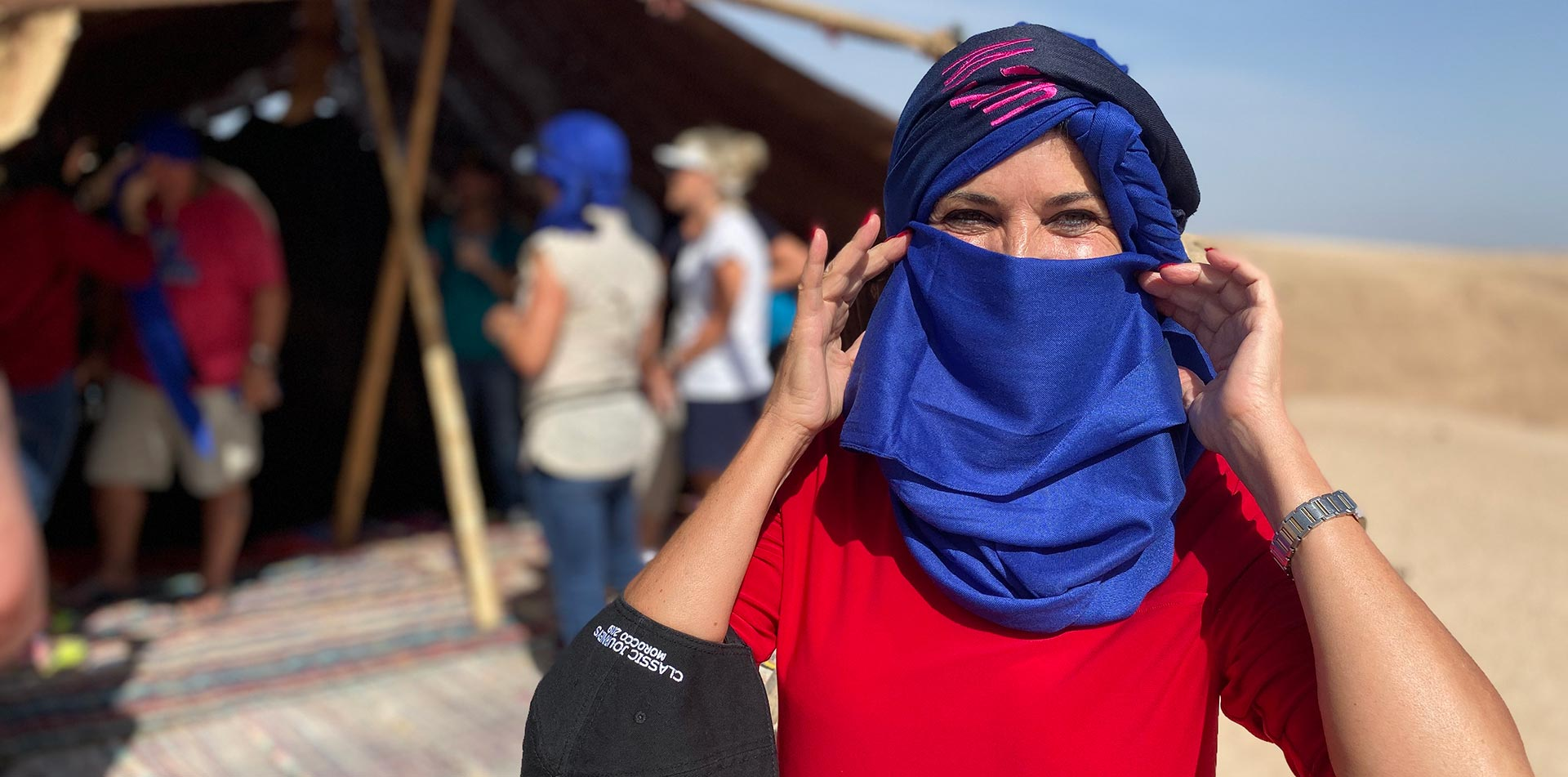 Africa Morocco Agafay Village happy woman wearing blue face covering and traditional headscarf - luxury vacation destinations