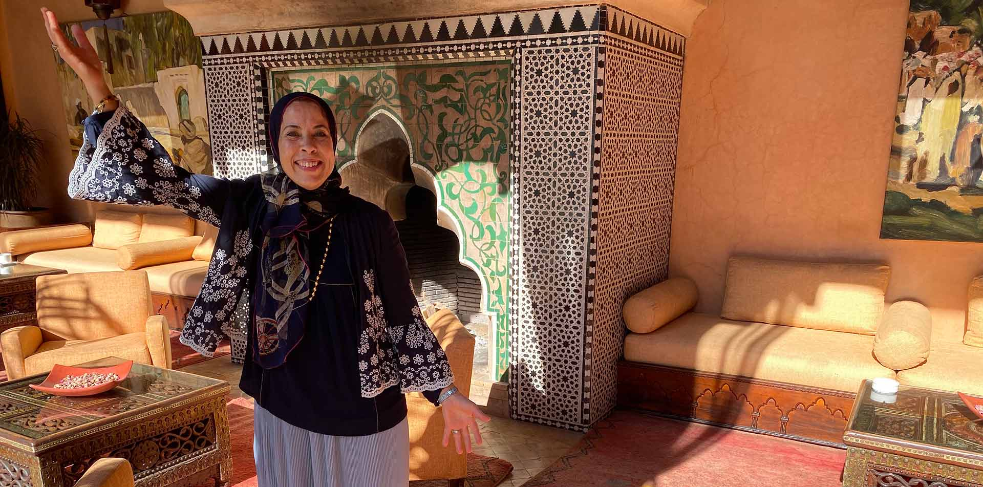 Africa Morocco happy woman wearing traditional head scarf smiling colorful mosaic fireplace - luxury vacation destinations