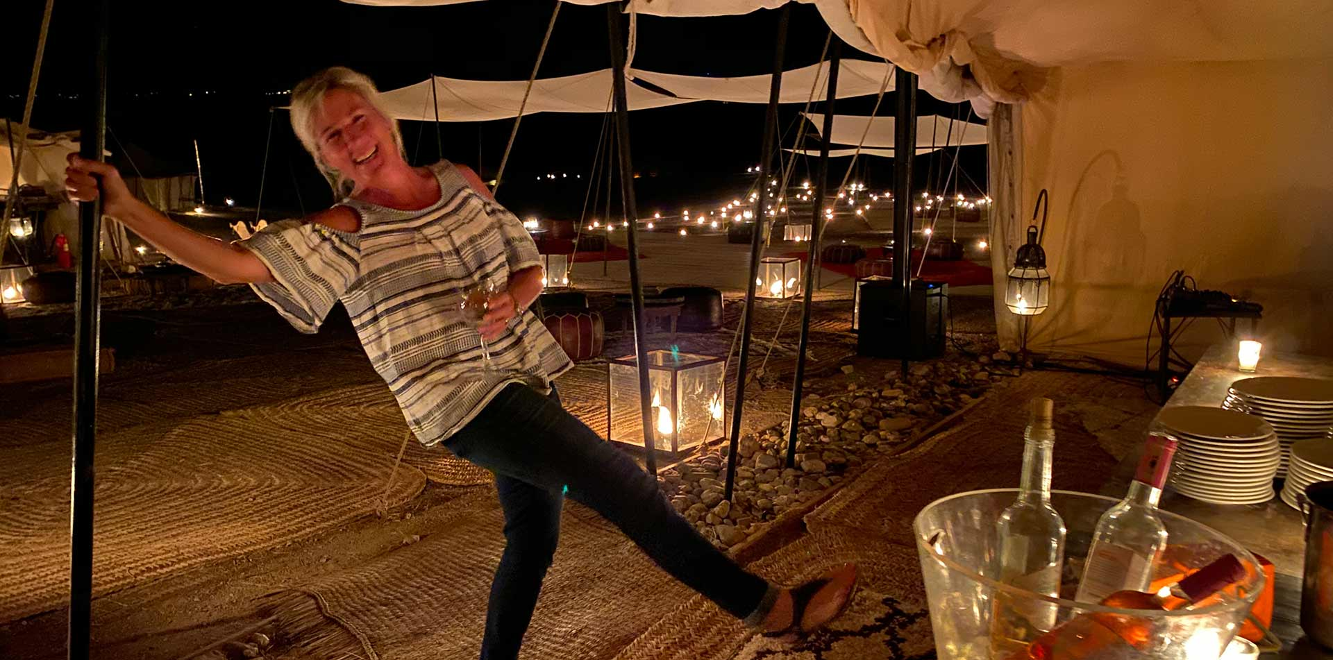 Africa Morocco Agafay Desert Scarabeo Camp bright lights at night woman smiling kicking leg - luxury vacation destinations