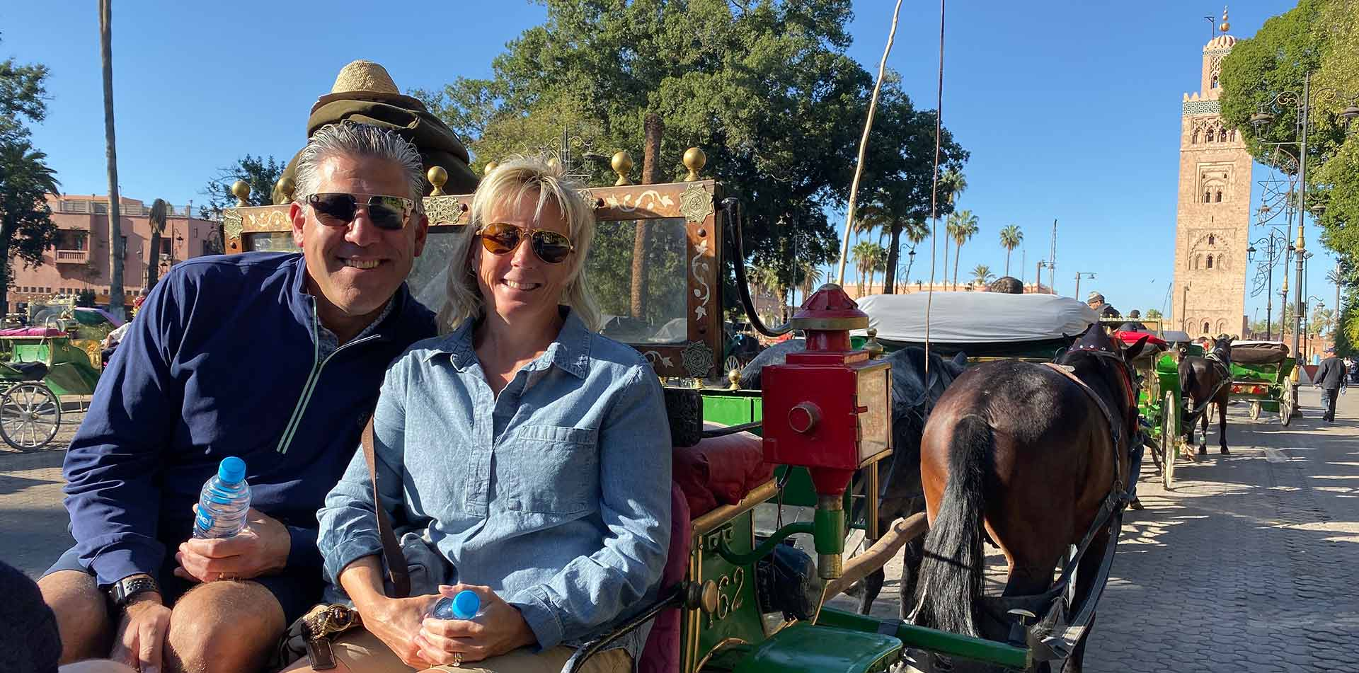 Africa Morocco Marrakesh happy smiling couple on horse-drawn carriage ride through the city - luxury vacation destinations