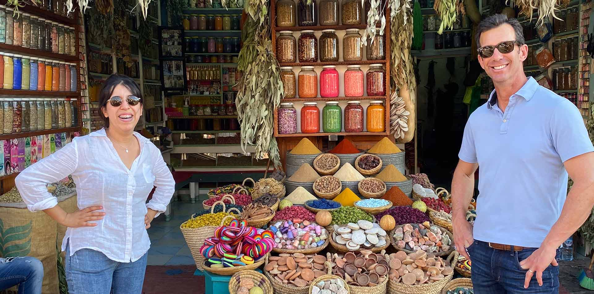 Africa Morocco happy man and woman smiling in front of colorful traditional spice market - luxury vacation destinations