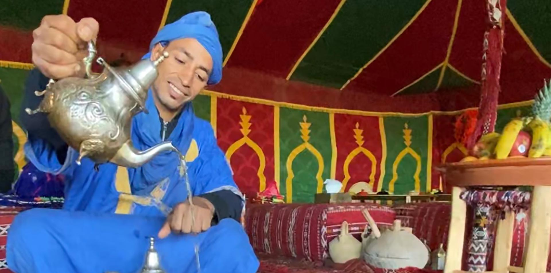 Africa Morocco Sahara Desert colorful Berber encampment Blue Man smiling pouring mint tea - luxury vacation destinations
