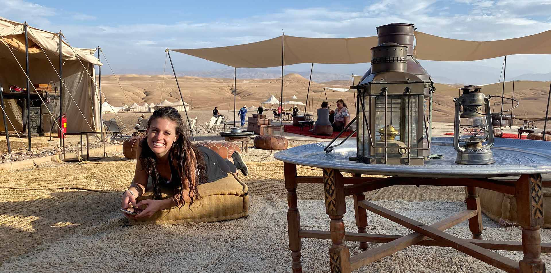 Africa Morocco Agafay Desert decorative Scarabeo Camp young girl smiling laying on pillow - luxury vacation destinations