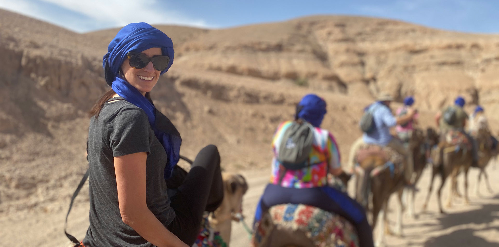 Africa Morocco Agafay Desert woman in head scarf smiling riding camel caravan - luxury vacation destinations