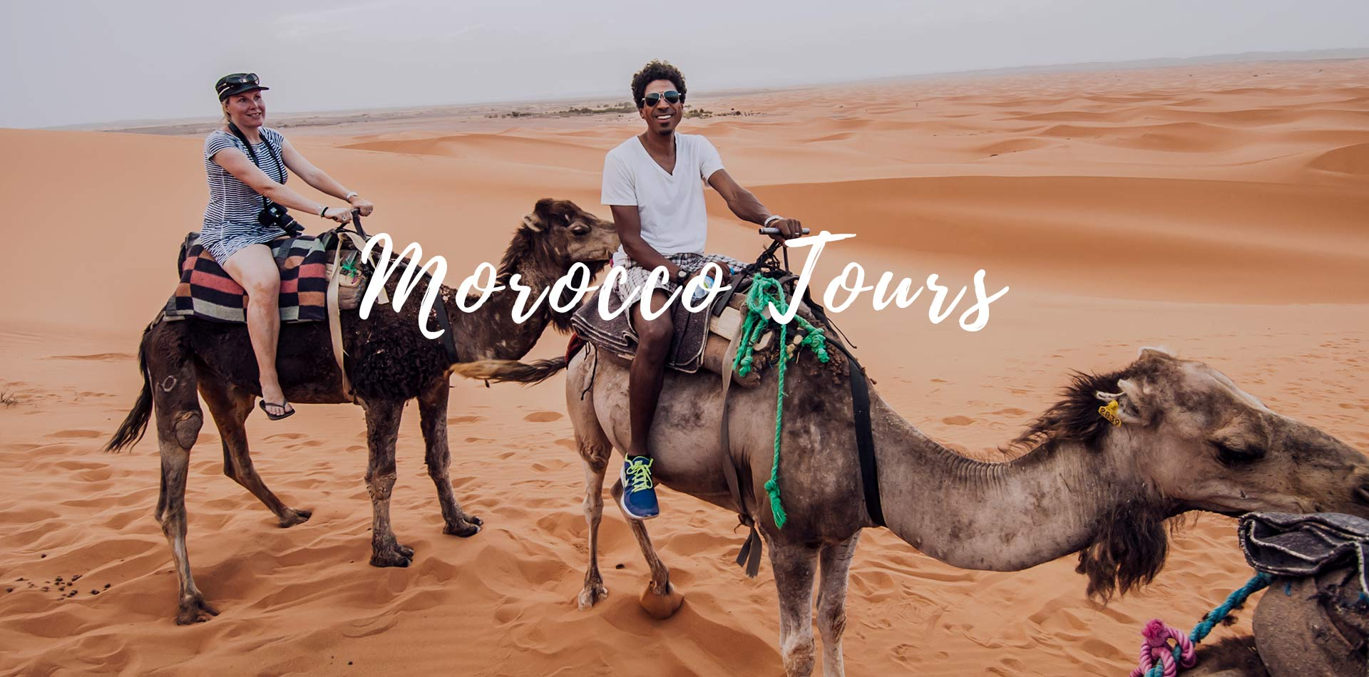 Africa Morocco tours Sahara Desert happy couple smiling riding camels in tan sand dunes - luxury vacation destinations