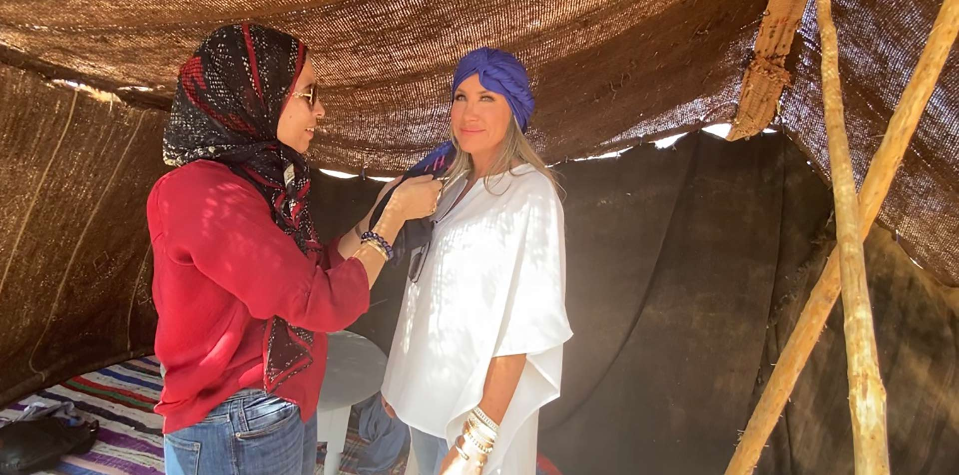 Africa Morocco Agafay Village women smiling wearing and tying head scarves in desert tent- luxury vacation destinations