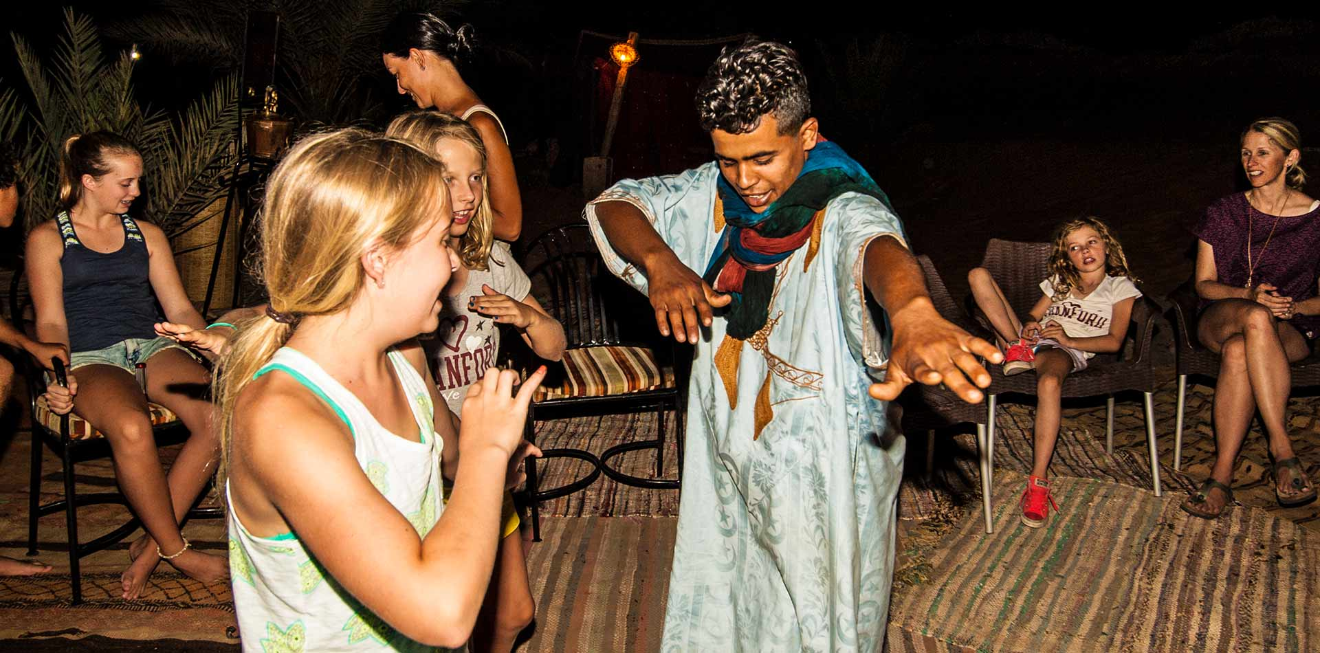 Africa Morocco Sahara Desert Merzouga Berber encampment kid's dancing with local Blue Man - luxury vacation destinations