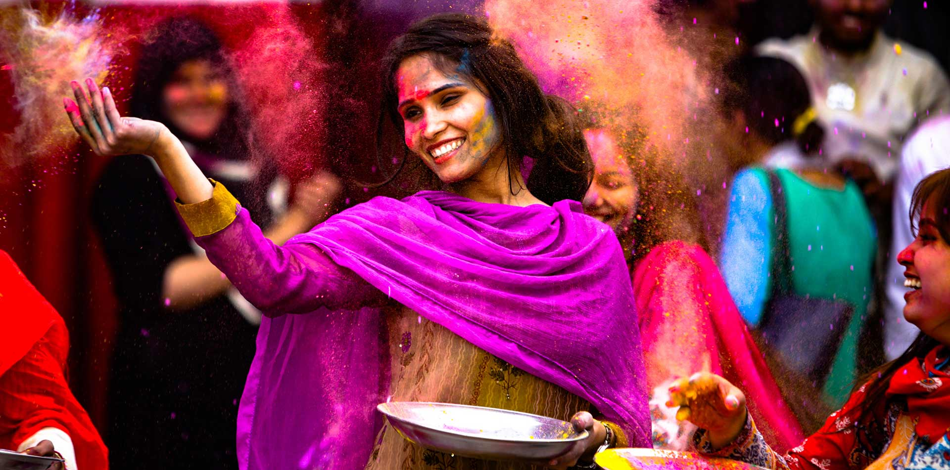 Asia India woman throwing powder dye to celebrate Holi Festival - luxury vacation destinations