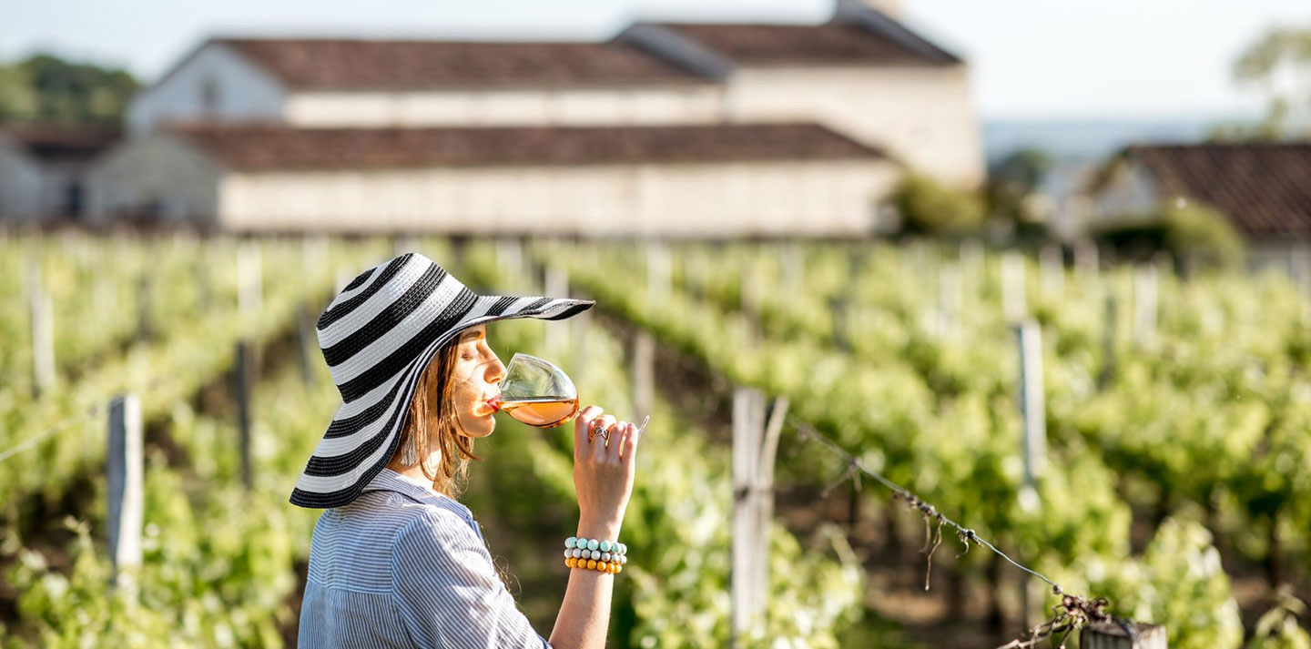 traveling woman drinking wine in grape vineyards at a winery food wine tours - luxury vacation destinations