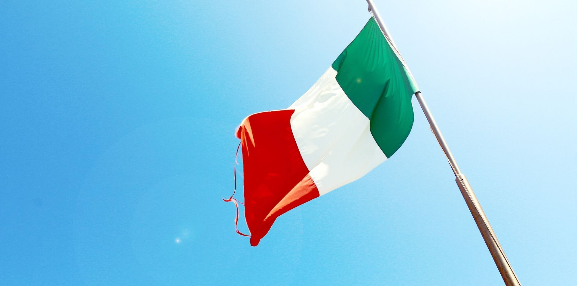 Europe Italy Italian Flag beautiful colors flowing in the wind blue sky white, red & green - luxury vacation destinations