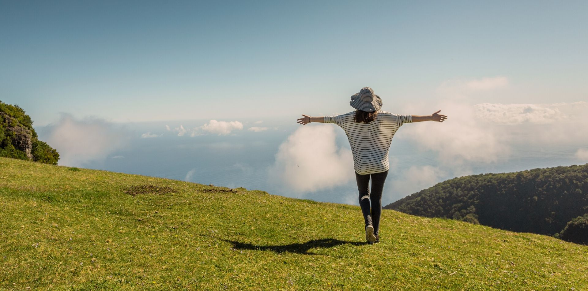 traveling woman with open arms in a field overlooking the ocean - luxury vacation destinations