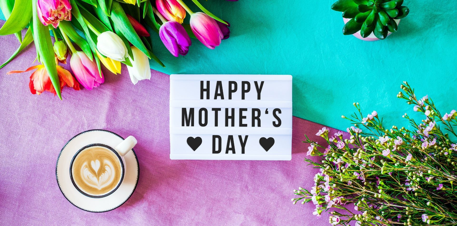 Happy Mother's Day sign with flowers and a latte on a colorful table