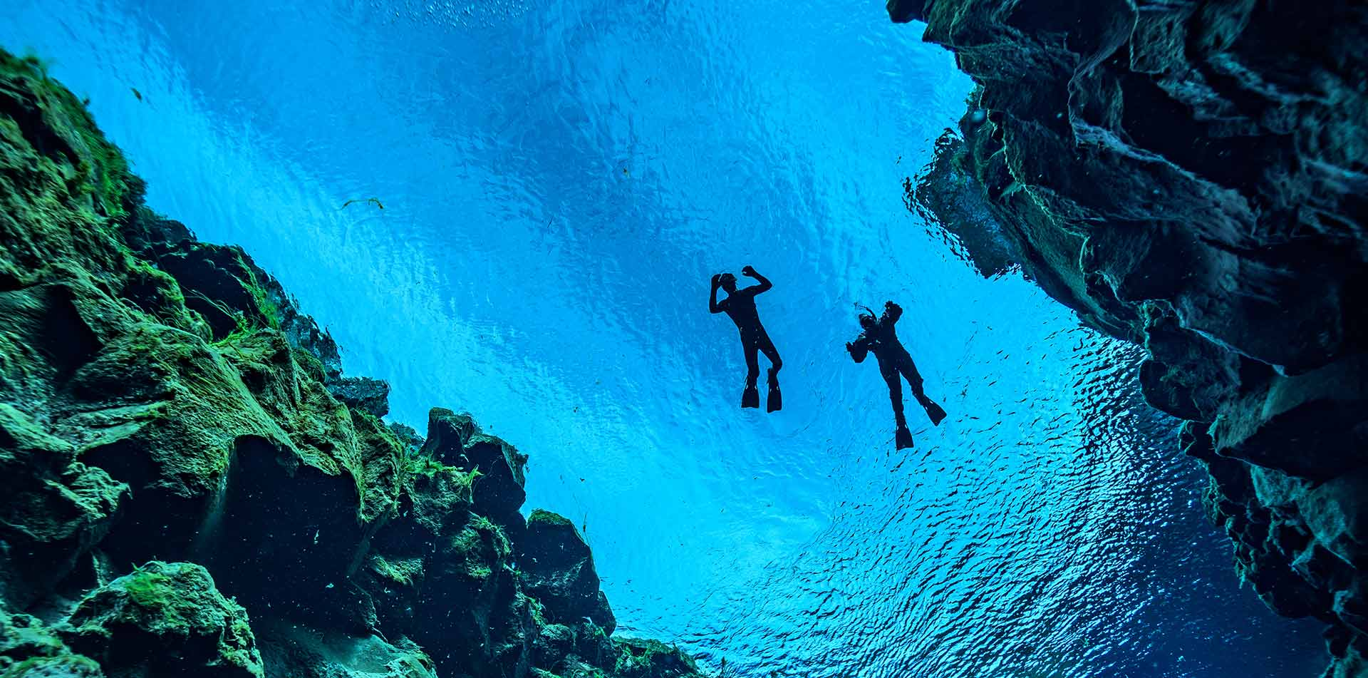 Europe Iceland Thingvellir National Park people snorkeling in blue Silfra fissure - luxury vacation destinations