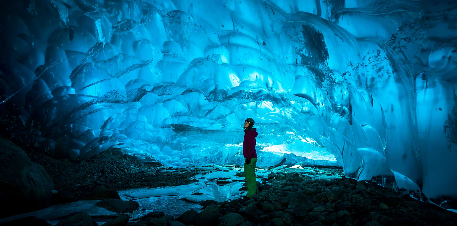Europe Iceland woman standing in bright blue ice cave under a glacier - luxury vacation destinations