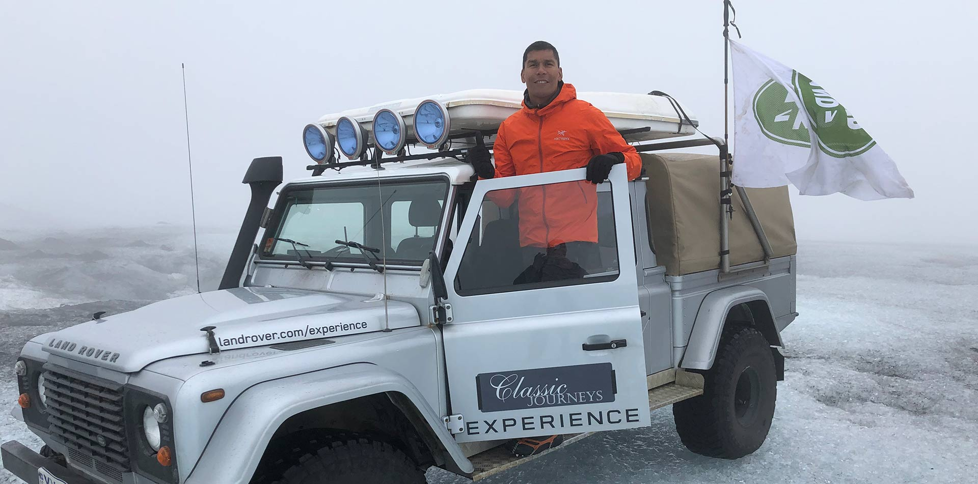 Europe Iceland man posing in Land Rover Defender smiling adventure beautiful glacier - luxury vacation destinations