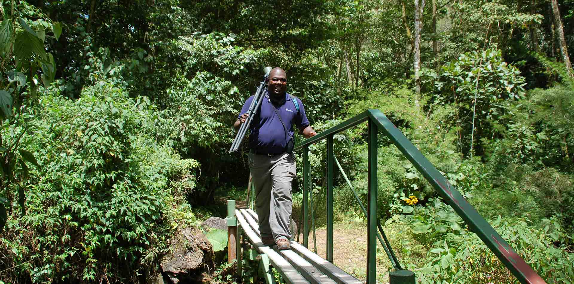 Central America Panama lush jungle local guide walking on bridge smiling carrying camera - luxury vacation destinations
