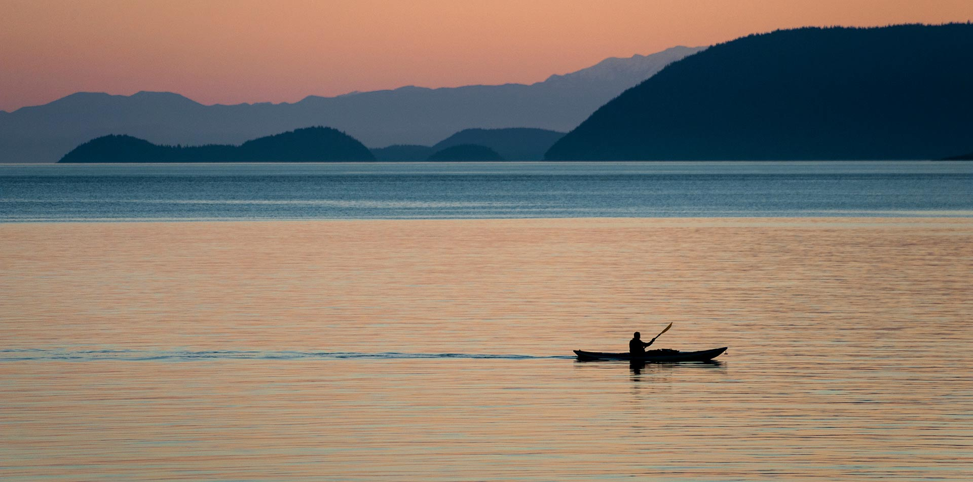 US Pacific Northwest Puget Sound scenic Orcas Island colorful sunset man kayaking calm water - luxury vacation destinations