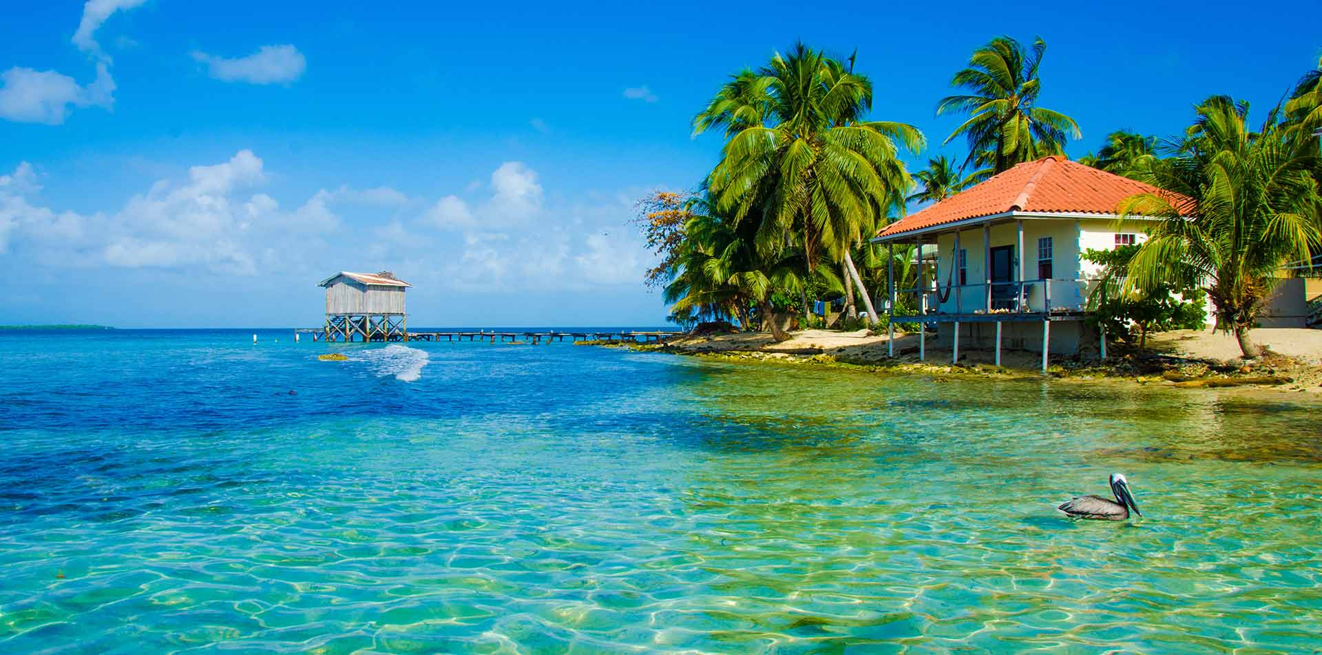 Central America Belize lush tropical island clear blue water beach bungalow scenic dock - luxury vacation destinations