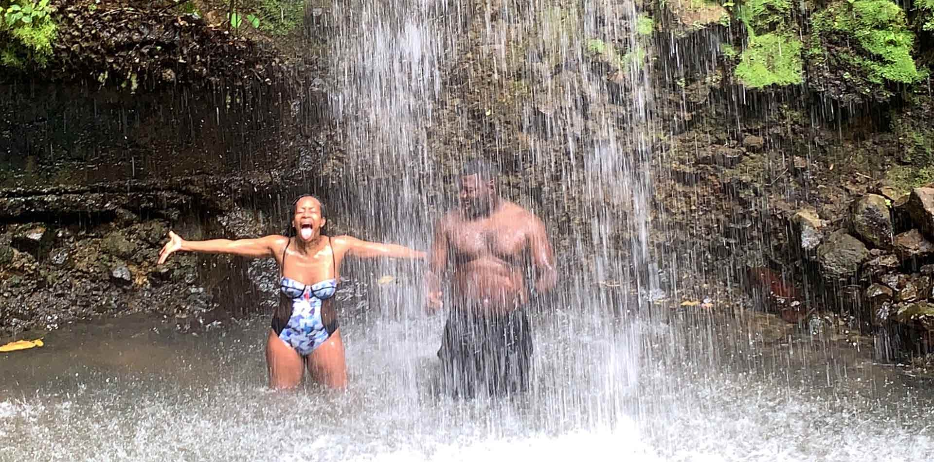 Latin America Caribbean St. Lucia couple under waterfall woman raising arms - luxury vacation destinations