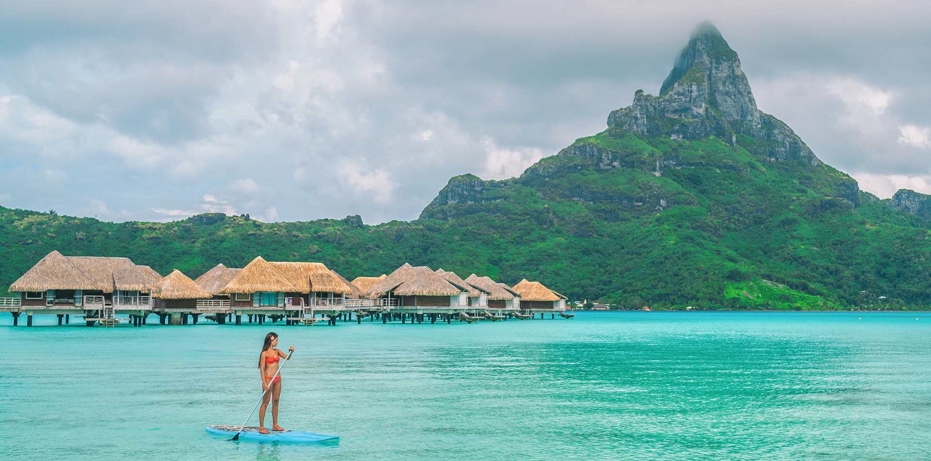 South Pacific Tahiti Bora Bora woman paddleboarding clear water thatched huts lush mountains - luxury vacation destinations