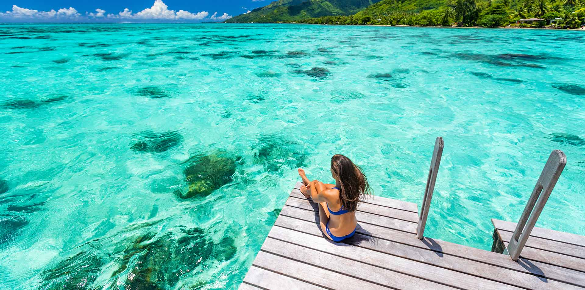 South Pacific Tahiti Bora Bora woman relaxing clear water lush landscape - luxury vacation destinations