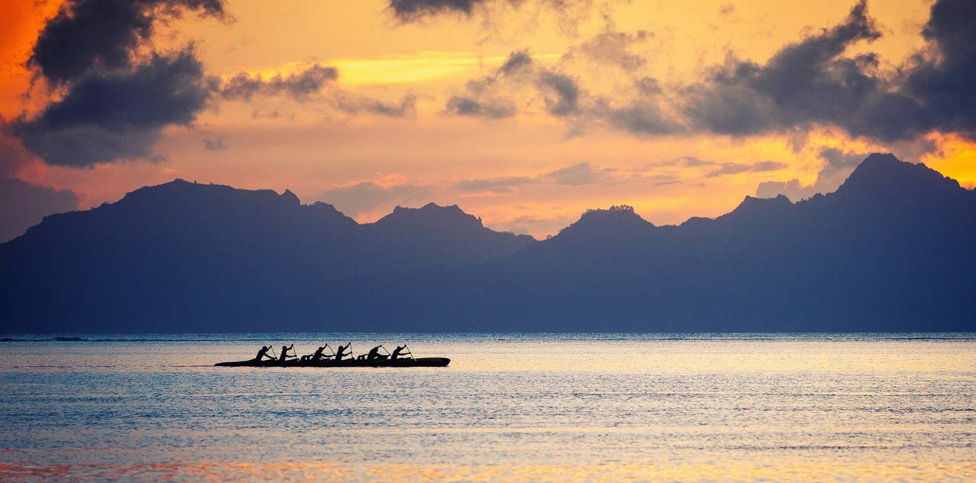 South Pacific Tahiti colorful sunset group rowing calm water scenic mountains  - luxury vacation destinations