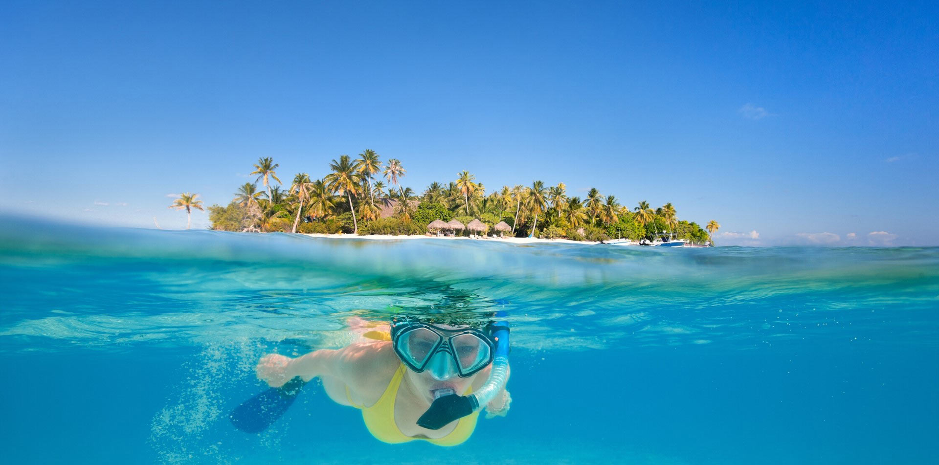 South Pacific Tahiti woman snorkeling clear blue water lush tropical island - luxury vacation destinations