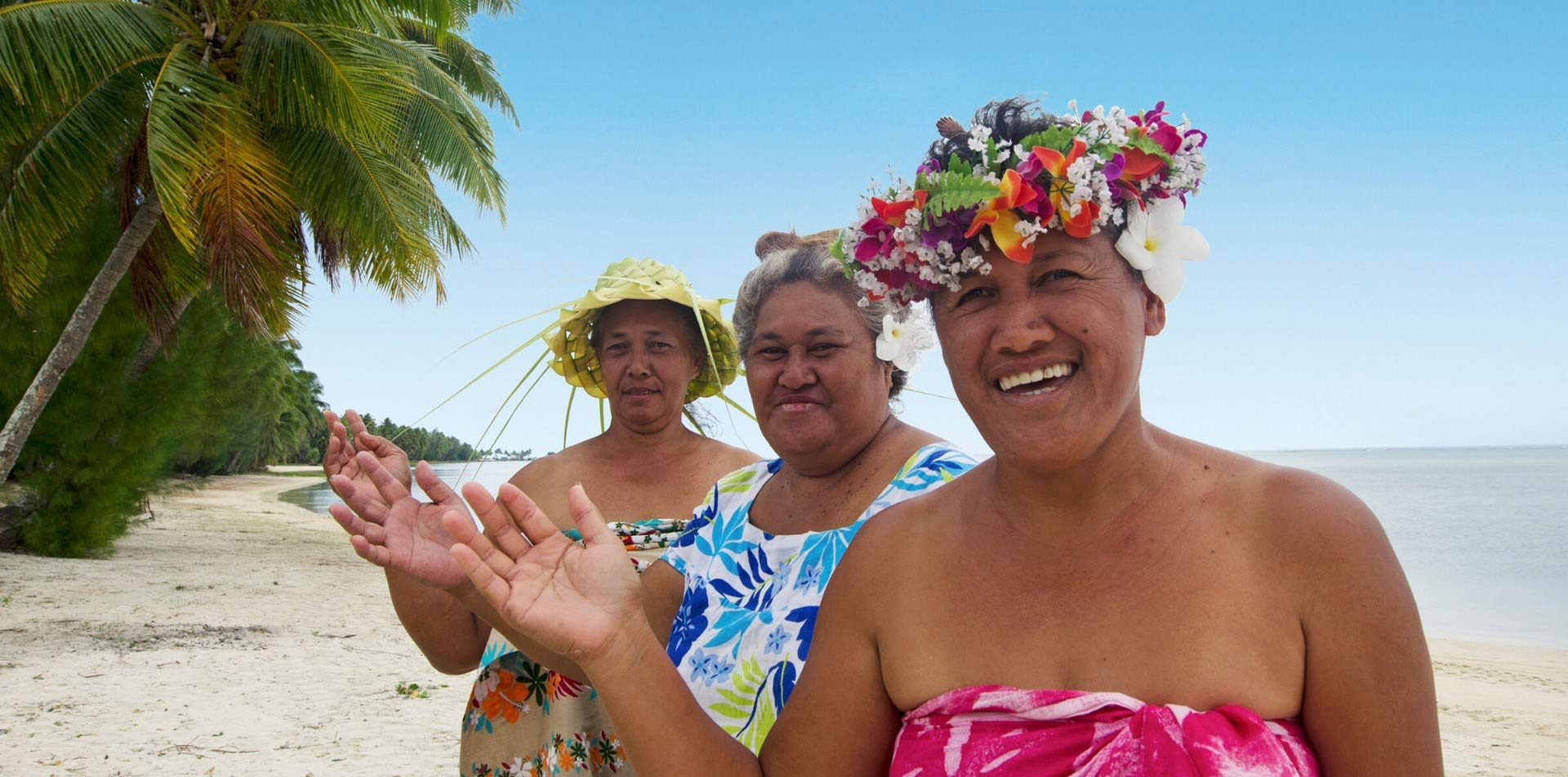 South Pacific Tahiti local women smiling waving colorful traditional attire tropical island - luxury vacation destinations