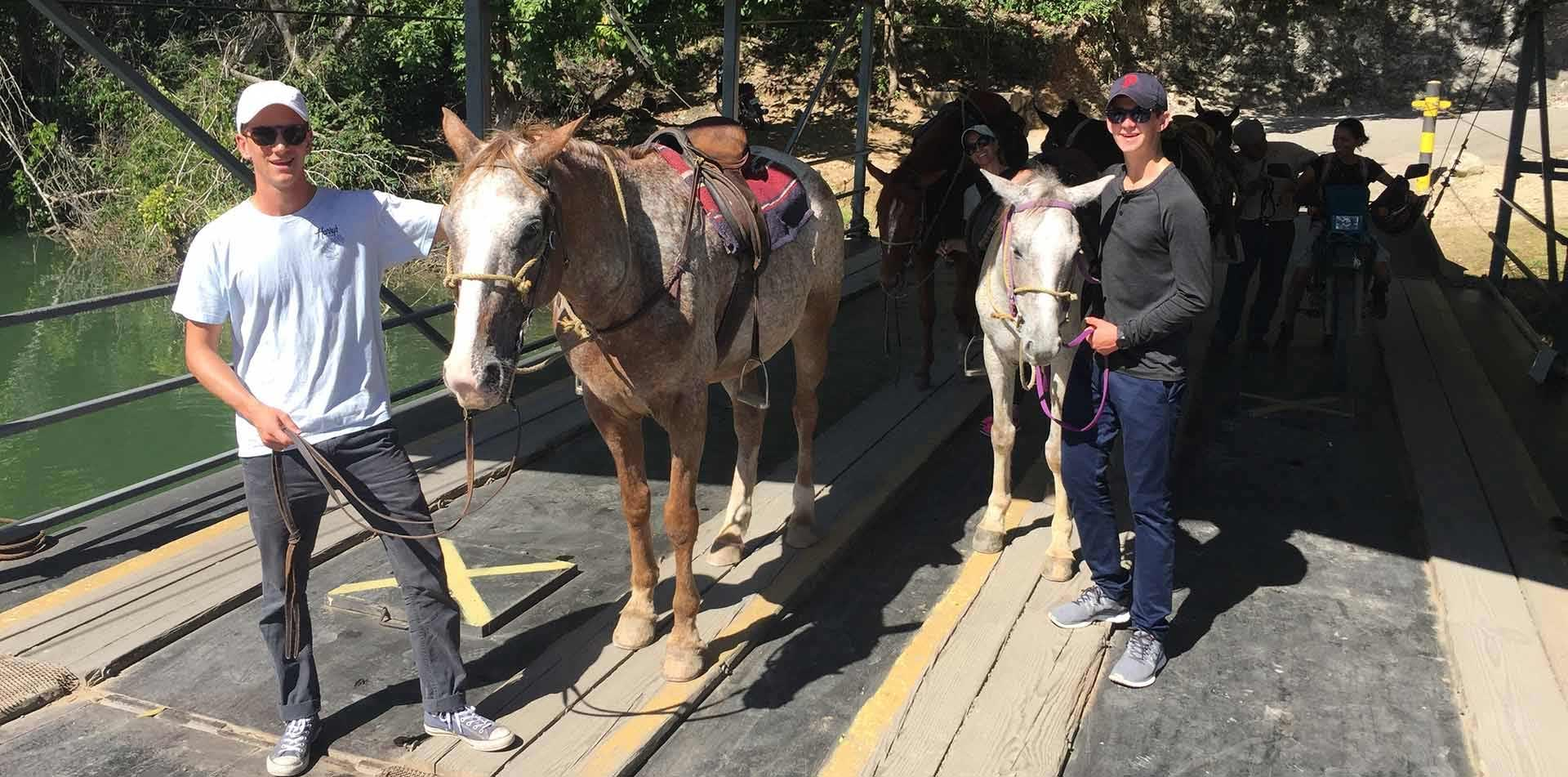 Central America Belize group standing next to horses on bridge smiling - luxury vacation destinations