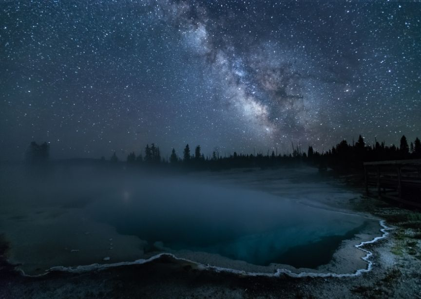 Yellowstone volcanic pool at night with stars above