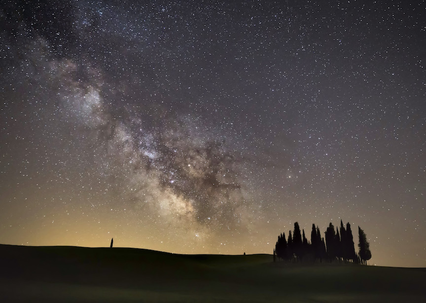 Italy Tuscany Field at Night with Trees silhouetted and starry skies milky way