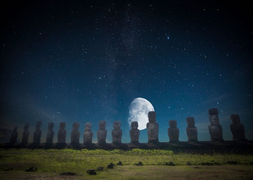 Easter Island Chile Moai Statues at night with moon and stars, grass in forefront